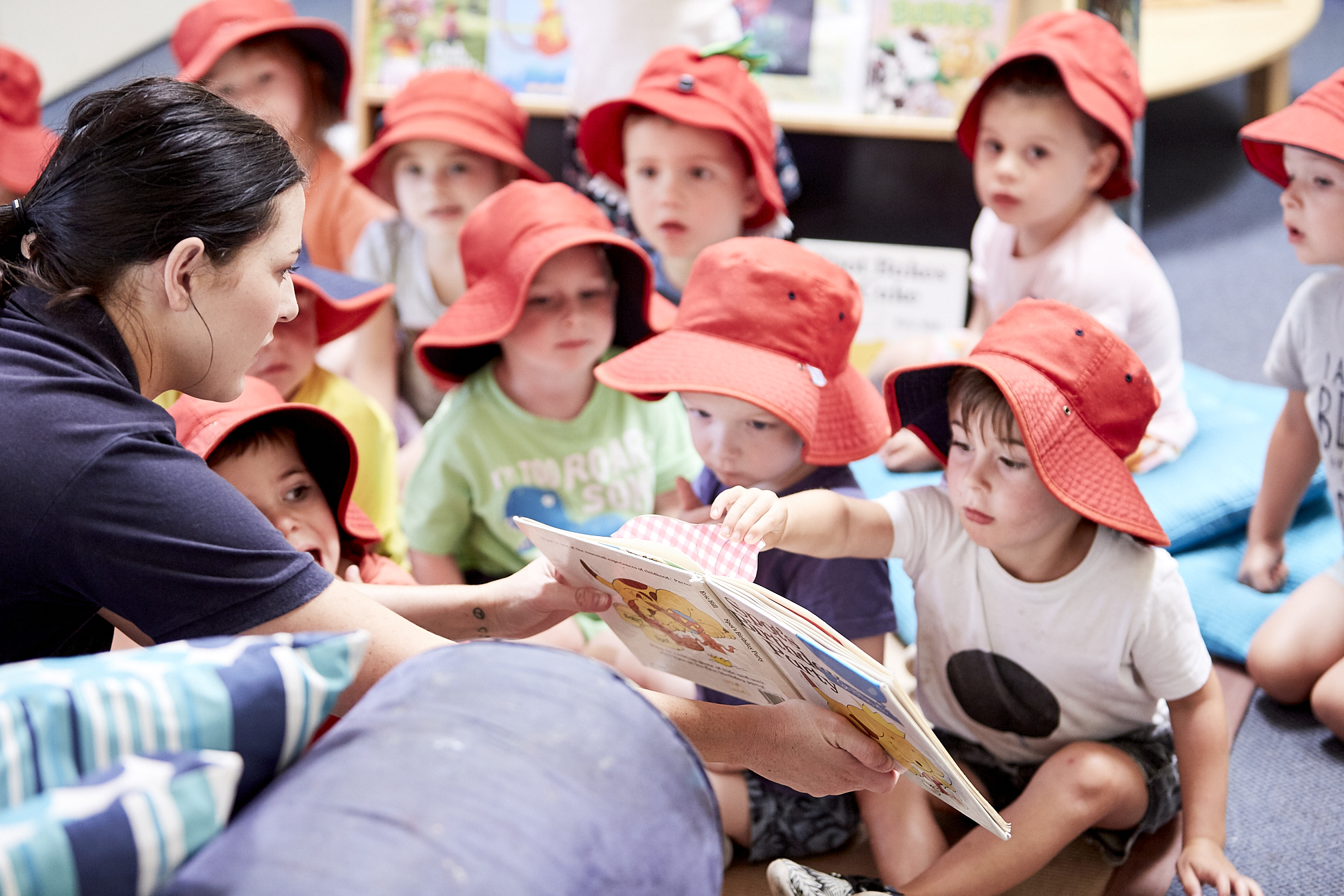 Group of young children being read to by child care educator at Kids Academy Erina Heights