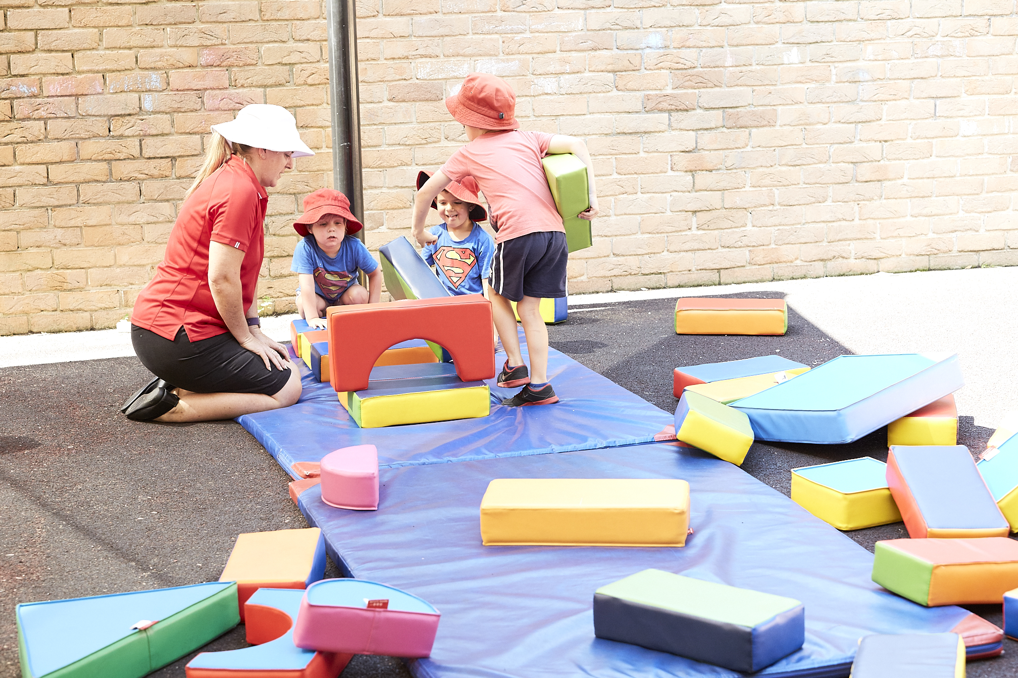 Child care educator playing with groups of children outside at Kids Academy Erina Heights