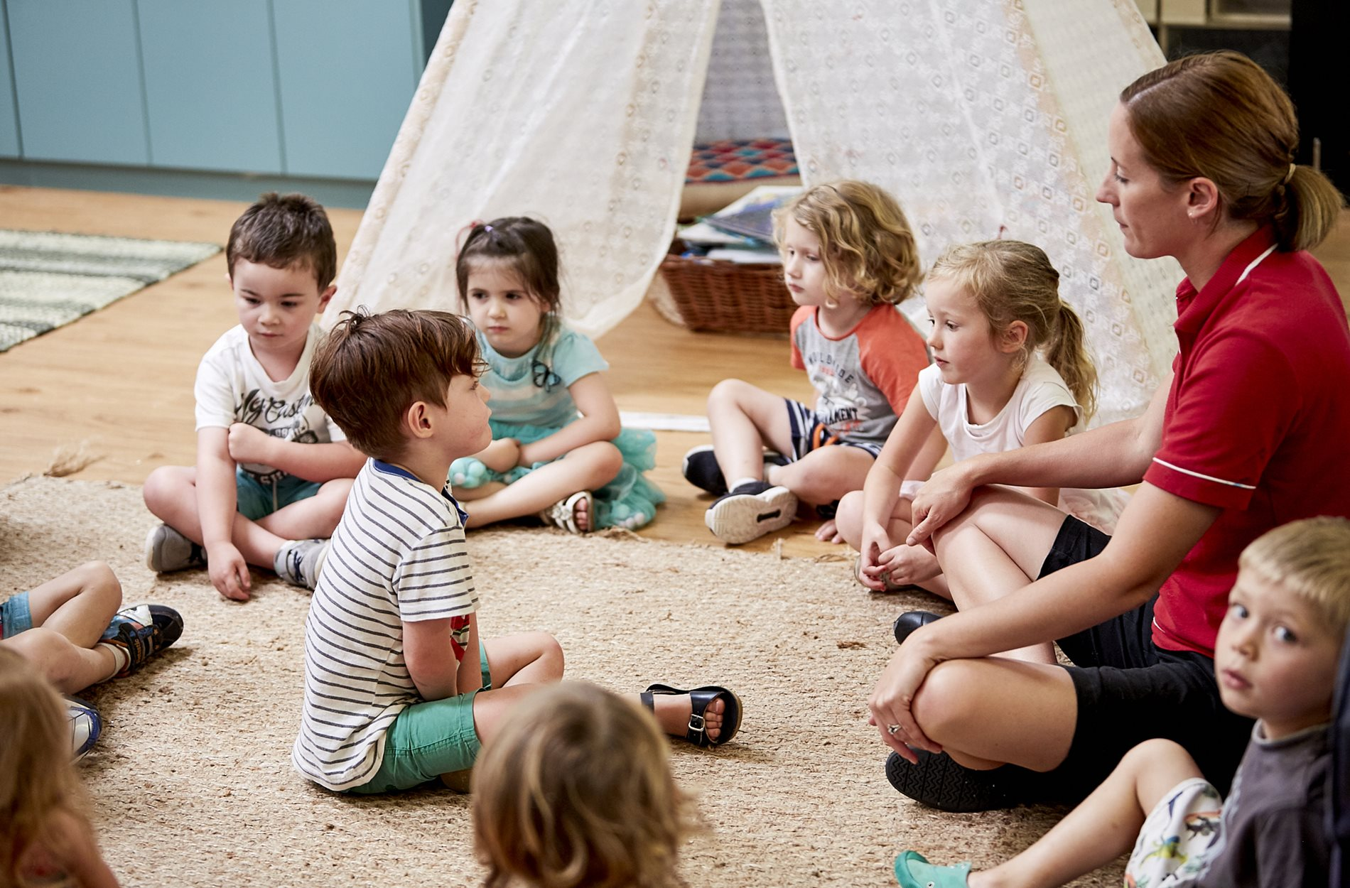 Group of children sitting in a circle in child care classroom at Kids Academy Erina Heights
