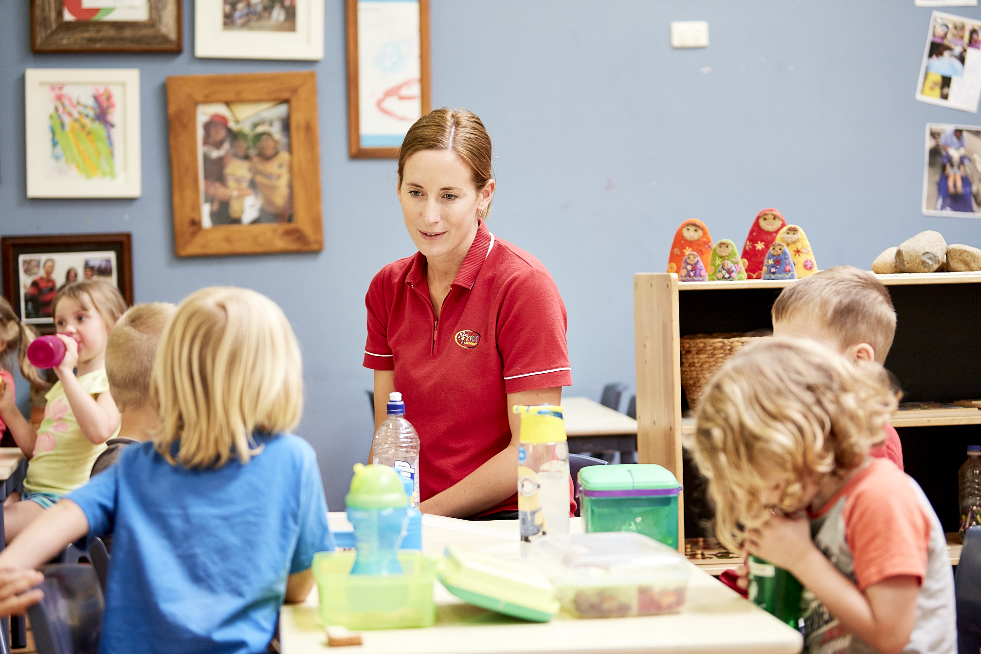 Child care educator interacting with group of children in child care classroom at Kids Academy Erina Heights