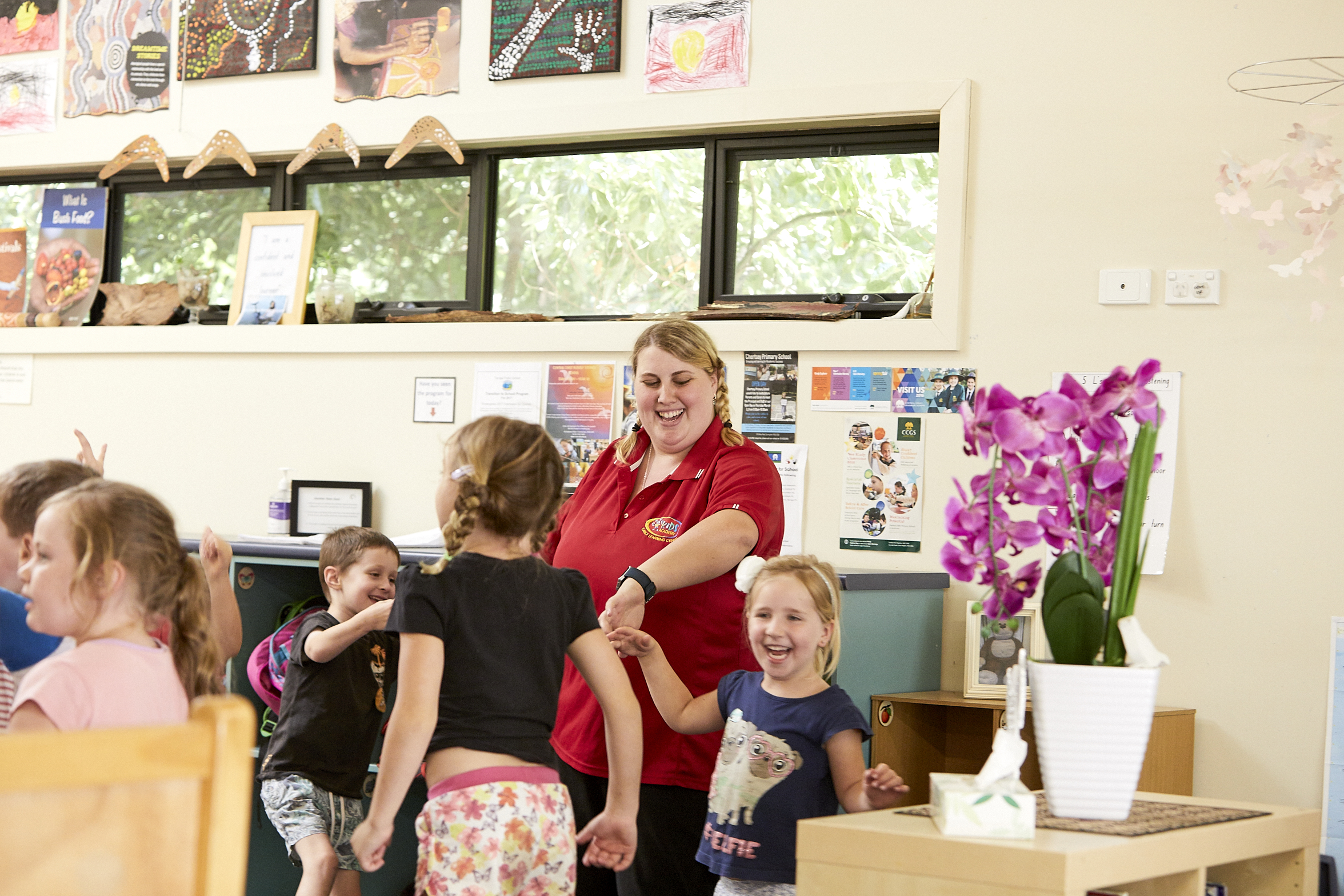 Child care educator dancing with group of children in classroom at Kids Academy Erina Heights